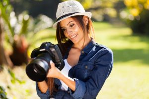 beautiful young female photographer checking pictures on her camera